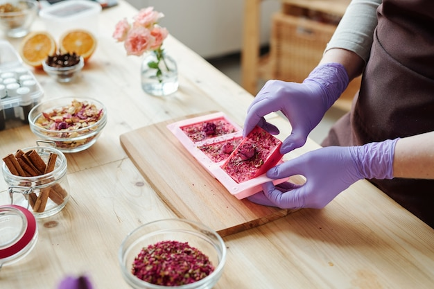 Hands of young woman in lilac rubber gloves taking out fresh handmade pink soap from silicone molds