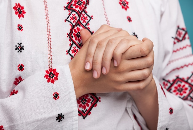 Hands of a young woman in the ukrainian national clothes