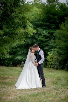 幸せな花嫁と花handsの手を繋いでいると庭の結婚式の日に歩いています。公園の森、幸せな結婚の瞬間を歩きながら手を繋いでいる魅力的なスタイリッシュな新婚夫婦の背面図