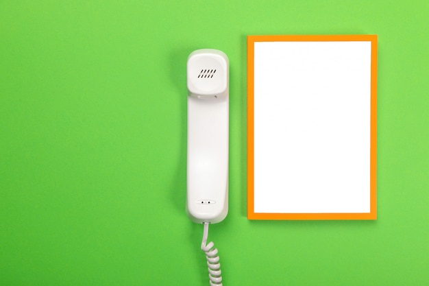 Handset from the phone and the white sheet lie isolated on green
