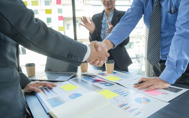Handshake after business team meeting to plan strategies to increase business income