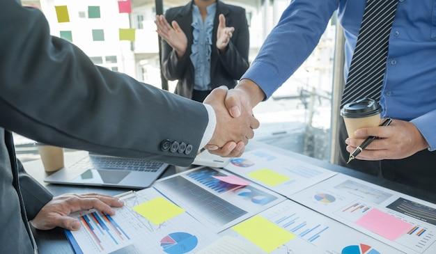 Рукопожатие после встречи команды деловых женщин и бизнесменов для планирования стратегии увеличения дохода от бизнеса. проведите мозговой штурм по анализу финансового графика и обсудите успех новой цели.