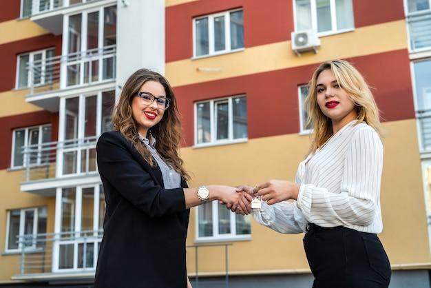 Рукопожатие после успешной сделки между риэлтором и новым владельцем с домом в фоновом режиме. концепция продажи
