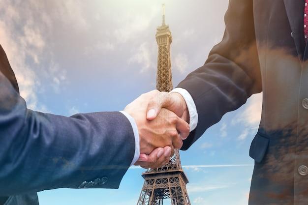 Handshake agreement of businessman with partnership on eiffel tower background
