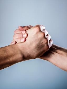 握手、腕。フレンドリーな握手、友達の挨拶。男性の手が握手で団結した。両手、孤立した腕、友人の手を助ける。