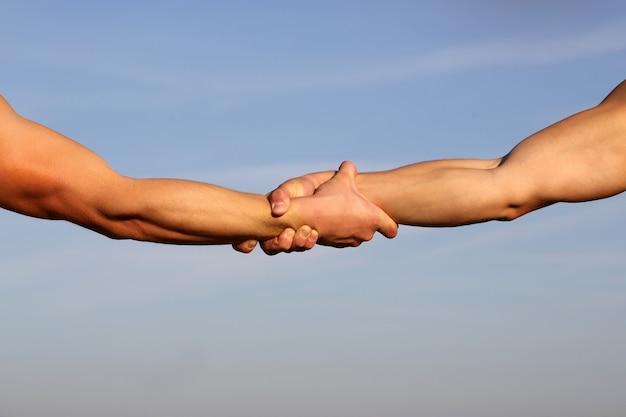 ハンドシェーク。腕。友情。フレンドリーな握手。友達の挨拶。チームワークと友情。閉じる。