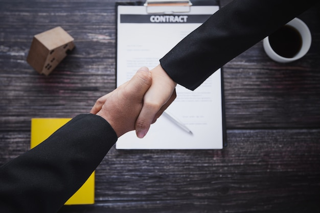 Handshake of bank agent office with customer or client, selling home, rent resident and buy apartment or real estate concept, top view of businessman shake hand with banker after successful negotiate