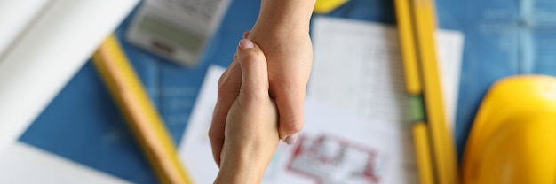 Рукопожатие между дизайнером и клиентом над документами в студии крупным планом, успешное одобрение
