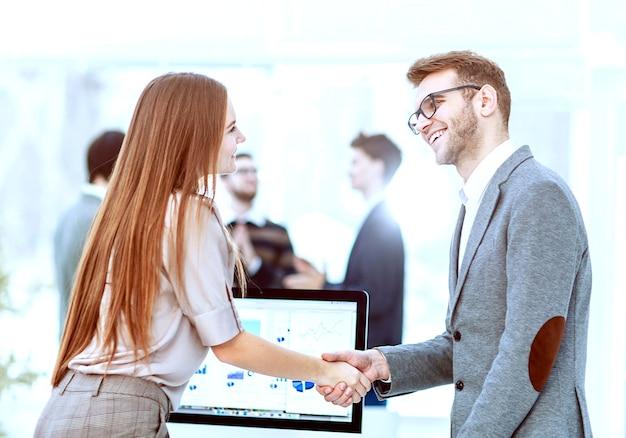 会社の発展のための投資計画を検討した後、弁護士とクライアントの間で握手します。写真にはテキスト用の空きスペースがあります。