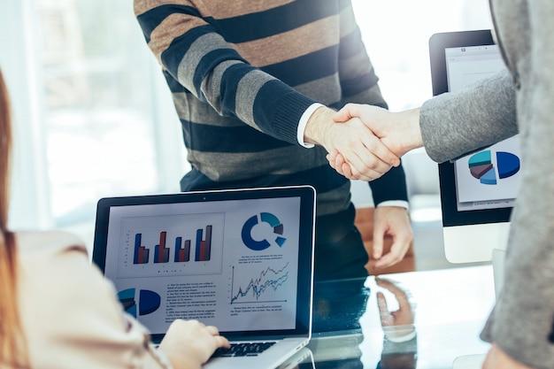 Рукопожатие между клиентом и менеджером компании возле рабочего места в современном офисе.