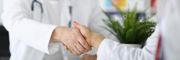 흰 코트를 입은 두 의사 간의 악수. 의료 성공적인 배치 개념