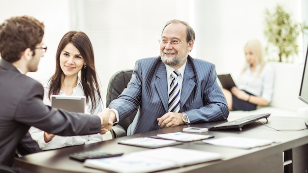 契約の金銭的条件について話し合った後、ビジネスパートナーと握手します。写真にはテキスト用の空きスペースがあります。