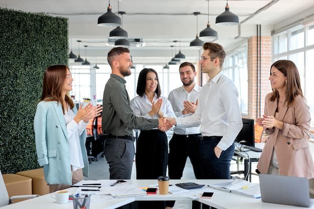 ハンドシェイクビジネスパートナーは、契約に署名することに同意します。国際貿易、会議への契約投資は、利益のために投資するというビジョンを持っています。成功した仕事をしている素敵な楽しいビジネスマンの側面図