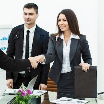 현대 사무실의 바탕 화면 근처 회의에서 악수하는 비즈니스 파트너 사진에는 텍스트를위한 빈 공간이 있습니다.