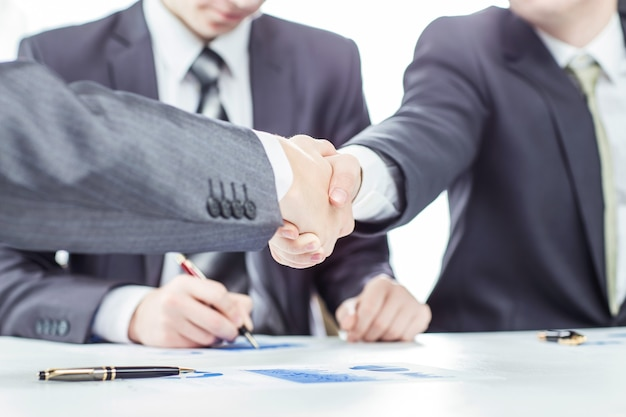 Handshake of business partners on the background of a lawyer and financial documents