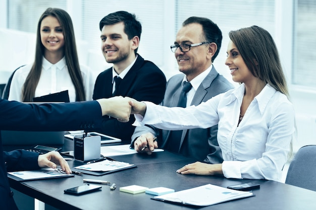 Handshake business partners at a meeting in creative office on
