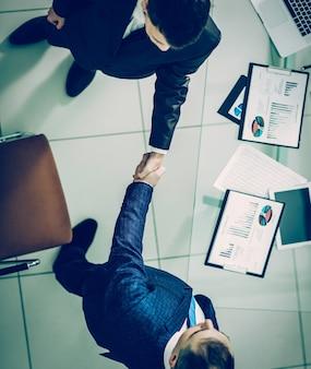 デスクトップの近くでビジネスパートナーと握手し、財務スケジュールを確認します。