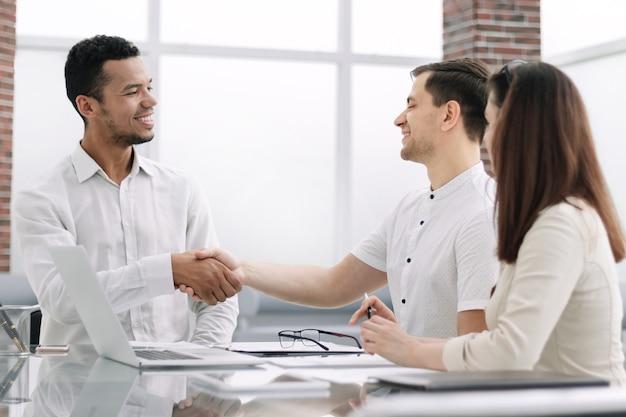 オフィスデスクに座っている握手ビジネスパートナー。