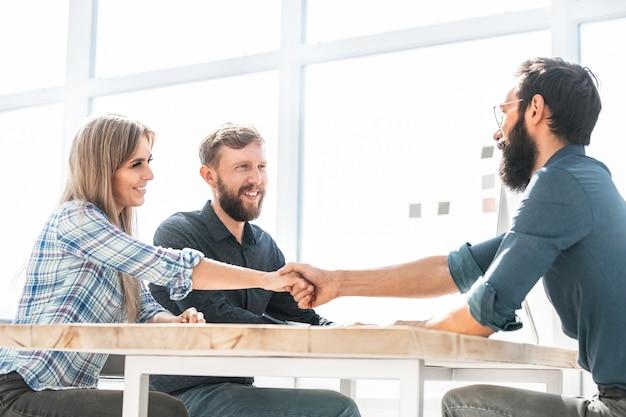 オフィスでの会議でビジネスマンと握手します。パートナーシップの概念