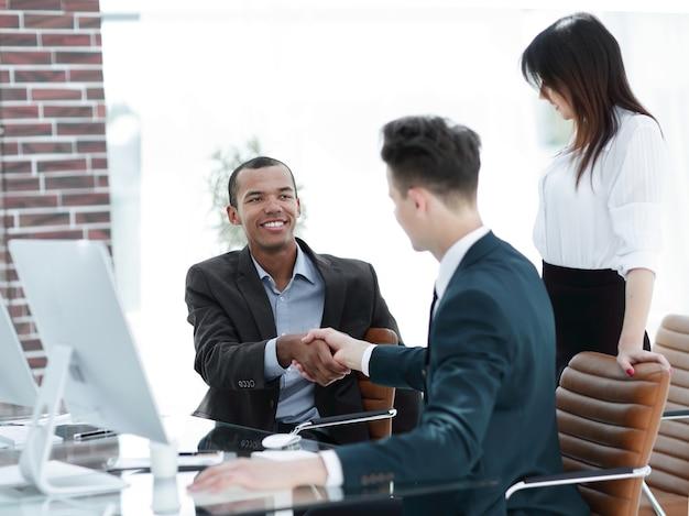 Рукопожатие деловых людей за столом в офисе.