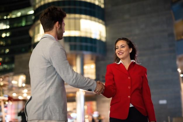 Handshake between business people outdoor at late evening