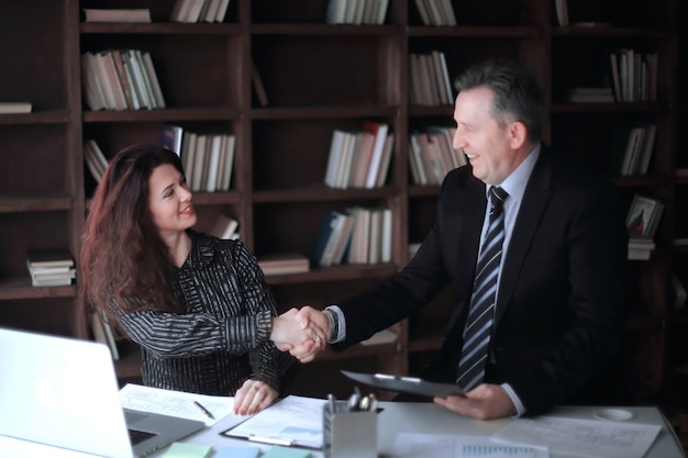 Handshake business woman with a business partner