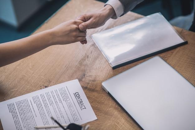 ハンドシェイク、取引。契約締結のサインとして握手する女性と男性の手