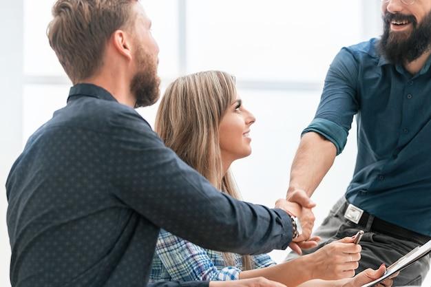 Рукопожатие сотрудников на рабочем месте в офисе. концепция успеха