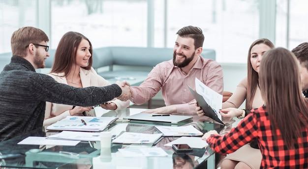 オフィスの職場での新しい契約について話し合った後、金融パートナーと握手する