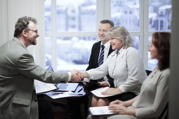 取引について話し合う前に、金融パートナーと握手します。