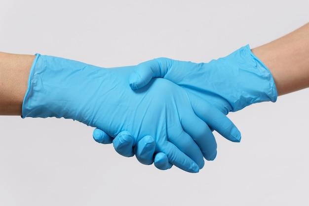 医療協力の握手。ラテックス手袋をはめた人々が挨拶を交わす。
