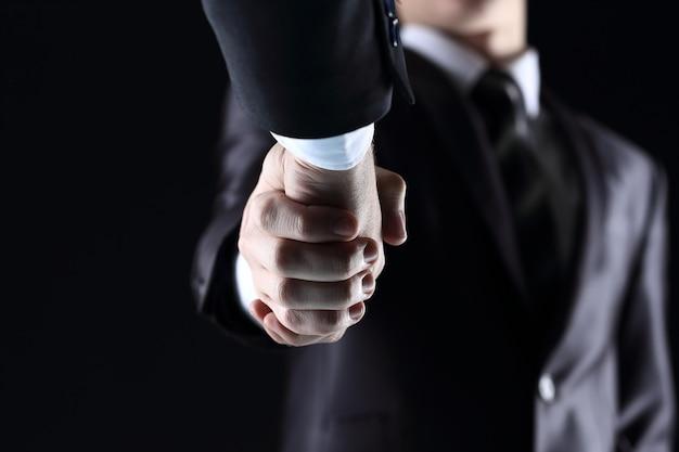 Рукопожатие - рука на темном фоне