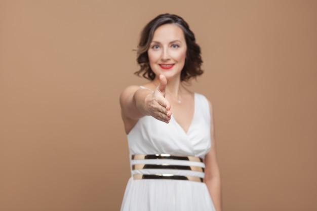 Рукопожатие. счастливая женщина зубастая улыбка и показывая приветственный знак. эмоционально выражающая женщина в белом платье, красных губах и темной вьющейся прическе. студийный снимок, закрытый, изолированный на бежевом коричневом фоне