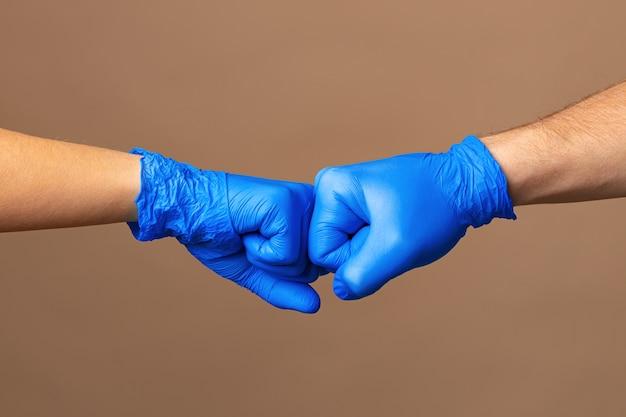 Рукопожатие в синих перчатках, концепция помощи. личная гигиена во время пандемии
