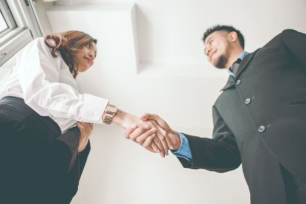 Handshake of male and female businessmen. focus on both hands.