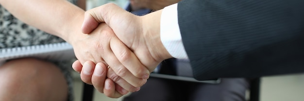 Handshake of man and woman closeup and cheering businessman in office. partner relationship with customers concept.