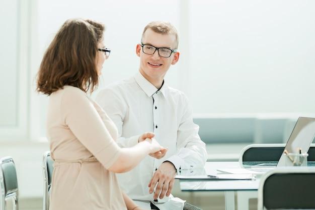 Рукопожатие менеджер и клиент за офисным столом концепция сотрудничества