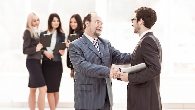 Менеджер рукопожатия и клиент на фоне бизнес-команды в современном офисе