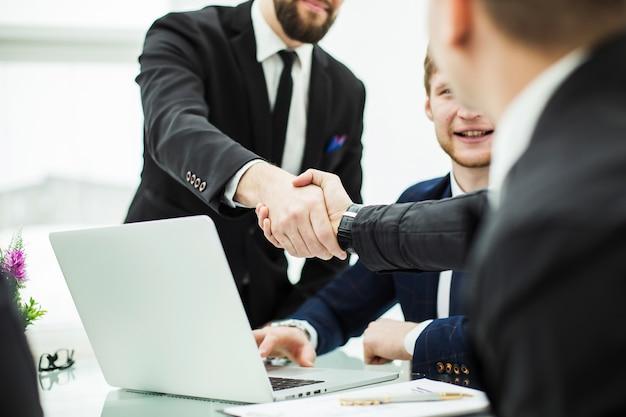 Рукопожатие менеджера и клиента после обсуждения финансового контракта на рабочем месте в офисе. на фото есть пустое место для вашего текста