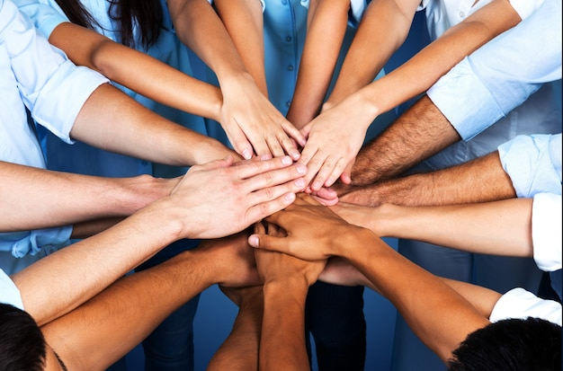 Handshake of many young business people, teamwork concept