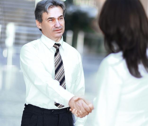 現代のオフィスの中心に立っているビジネスマンとビジネスウーマンの握手
