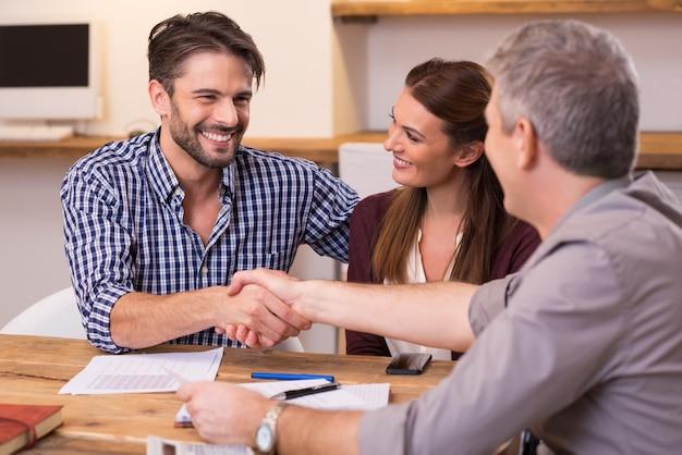 オフィスで幸せな若いカップルと成熟したマネージャーの握手。契約書に署名する会議中にビジネスマン握手。手を振って幸せな男が彼の財務顧問を聖霊降臨します。