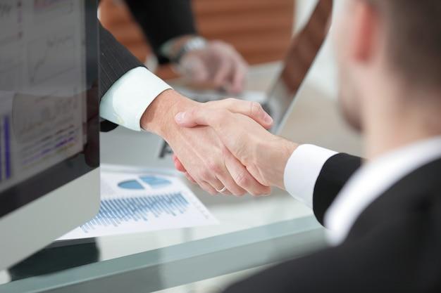 机の上のビジネスパートナーの握手 Premium写真