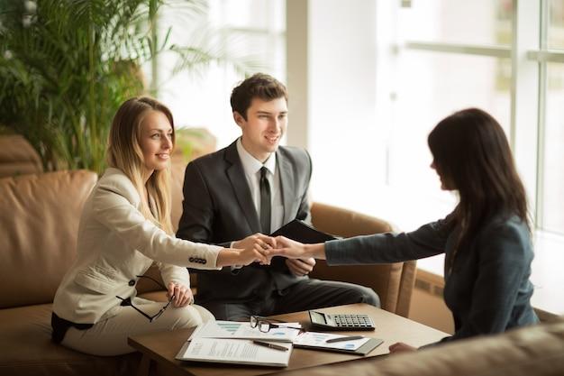 Рукопожатие деловых партнеров после обсуждения нового финансового контракта на рабочем месте в офисе