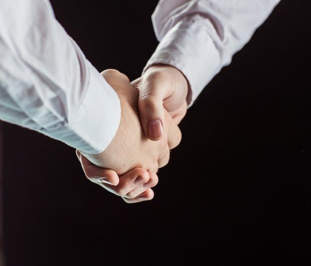 黒の背景にビジネスパートナーの握手。