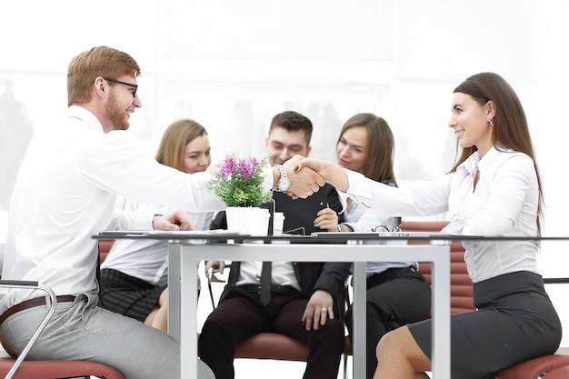 Рукопожатие деловых партнеров на столе в офисе