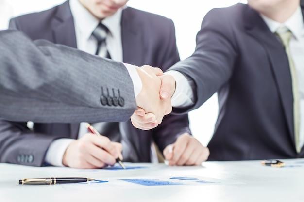 弁護士と財務書類の背景にあるビジネスパートナーの握手