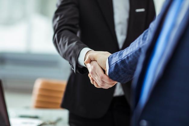 明るいオフィスを背景にビジネスパートナーの握手。