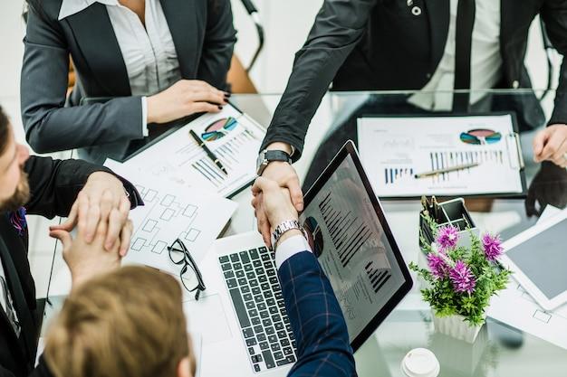 Рукопожатие деловых партнеров на фоне финансовых графиков, лежащих на рабочем месте