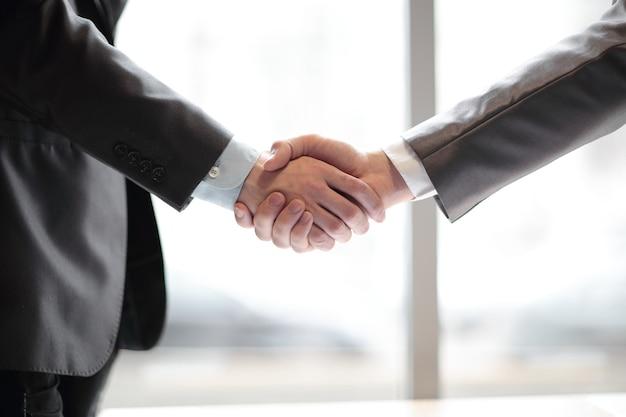 ぼやけたオフィスの背景にビジネスマンの握手